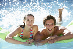 Pares novos que têm o divertimento com piscina inflável do colchão de ar junto Fotografia de Stock