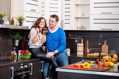 Pares novos que têm o divertimento na cozinha Fotografia de Stock Royalty Free