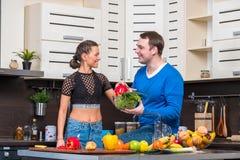 Pares novos que têm o divertimento na cozinha Foto de Stock