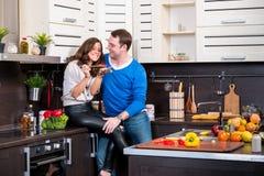 Pares novos que têm o divertimento na cozinha Imagem de Stock Royalty Free