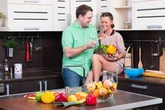 Pares novos que têm o divertimento na cozinha Fotos de Stock