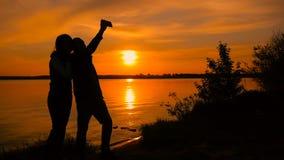 Pares novos que tomam a foto do selfie na praia durante o por do sol, movimento lento super vídeos de arquivo