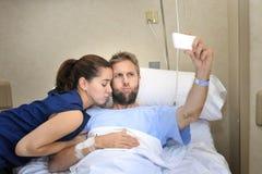 Pares novos que tomam a foto do selfie na sala de hospital com o homem que encontra-se na cama da clínica Fotografia de Stock