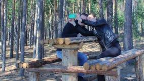 Pares novos que tomam o selfie com o telefone celular que senta-se no banco na floresta do parque video estoque