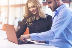 Pares novos que trabalham junto em um portátil no escritório conceitos dos trabalhos de equipa fotografia de stock