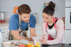 Pares novos que trabalham na esposa da cozinha doméstica junto depois da receita Fotos de Stock