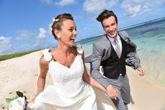 Pares novos recentemente casados que correm na praia Fotos de Stock Royalty Free