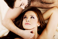 Pares novos relaxado que encontram-se na cama Fotos de Stock Royalty Free