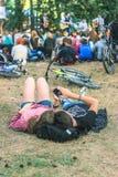 Pares novos relaxado que encontram-se na grama e no telefone de observação Fotos de Stock Royalty Free