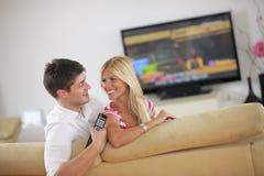 Pares novos relaxado que olham a tevê em casa fotos de stock royalty free