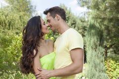 Pares novos românticos aproximadamente a beijar no parque fotografia de stock royalty free