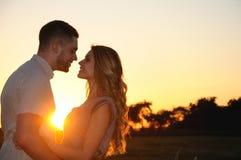 Pares novos românticos felizes no amor no por do sol imagens de stock royalty free