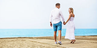 Pares novos românticos na praia Imagens de Stock Royalty Free