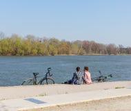 Pares novos românticos nas camisas de manta que sentam-se no banco de rio com bicicletas Conceito vivo ativo Espaço para o texto fotografia de stock royalty free
