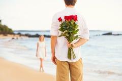 Pares novos românticos no amor, ramalhete da surpresa da terra arrendada do homem de r imagem de stock royalty free