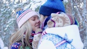 Pares novos românticos que beijam e que apreciam seu tempo na floresta do inverno filme