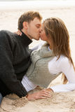 Pares novos românticos que beijam na praia Fotografia de Stock