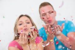 Pares novos românticos que comemoram o partido com confetes fotografia de stock royalty free