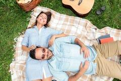 Pares novos românticos que relaxam em um parque Encontrando-se em suas partes traseiras em uma cobertura do piquenique, afagando foto de stock royalty free