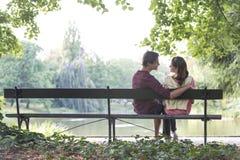 Pares novos românticos que sentam-se no banco de parque pelo lago Fotografia de Stock