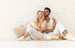 Pares novos Sit On Pillows Floor, homem latino-americano feliz e café da manhã Tray Lovers In Bedroom da mulher fotografia de stock royalty free