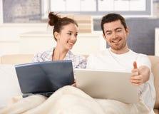 Pares novos usando o portátil na cama em casa que sorri Imagens de Stock