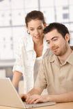 Pares novos usando o portátil junto que sorri em casa Fotos de Stock Royalty Free