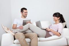 Pares novos usando portáteis no sofá Fotos de Stock Royalty Free