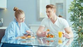 Pares novos usando a tabuleta digital ao comer o café da manhã na mesa de cozinha filme