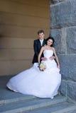 pares Nuevo-casados cerca de la pared de piedra Foto de archivo libre de regalías