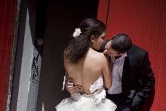 Pares nupciais bonitos novos que beijam contra a construção vermelha Fotografia de Stock Royalty Free