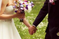 Pares nupciais bonitos que têm o divertimento no parque em seu ramalhete da flor do dia do casamento Fotografia de Stock Royalty Free