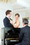 Pares nupciais na frente de um piano Imagens de Stock Royalty Free