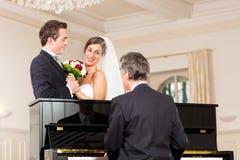 Pares nupciais na frente de um piano Imagem de Stock Royalty Free