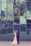 Pares nupciales cerca del edificio hecho del vidrio Foto de archivo libre de regalías