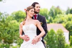 Pares nupciales en el parque, novio que detiene a la novia Imagen de archivo