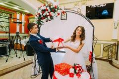 Pares nupciales felices con los presentes en el banquete de boda Imágenes de archivo libres de regalías