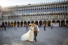 Pares nupciales hermosos en la puesta del sol en las calles de Venecia Imágenes de archivo libres de regalías