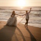 Pares nupciales hermosos jovenes que caminan a lo largo de la playa en la salida del sol Fotografía de archivo