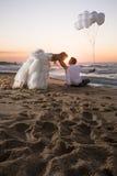 Pares nupciales hermosos jovenes que se relajan a lo largo de la playa en la salida del sol Imagen de archivo libre de regalías