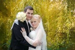 Pares nupciales, mujer feliz del recién casado y hombre abrazando en parque verde Fotografía de archivo libre de regalías