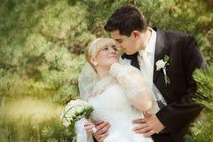 Pares nupciales, mujer feliz del recién casado y hombre abrazando en parque verde Imagen de archivo