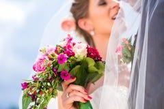 Pares nupciales que se besan debajo de velo en la boda Fotos de archivo libres de regalías