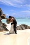 Pares nupciales románticos en la playa Foto de archivo libre de regalías