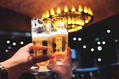 Pares o amigo que hacen alegrías con un vaso de cerveza para celebrar en restaurante, barra o café, imagen para Oktoberfest o ale foto de archivo libre de regalías