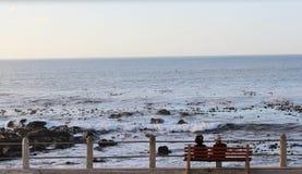 Pares o amigos que se sientan en un banco por la playa Imagen de archivo