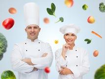 Pares o cocineros felices del cocinero sobre fondo de la comida Fotografía de archivo