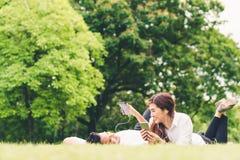 Pares o estudiantes universitarios preciosos asiáticos jovenes que escuchan la música junto en el jardín, con el espacio de la co Imágenes de archivo libres de regalías