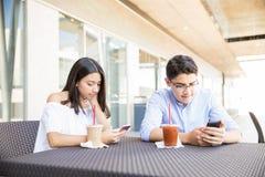 Pares obsesionados usando smartphones en alameda de compras Fotos de archivo