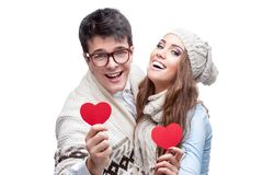 Pares ocasionais alegres novos que prendem corações vermelhos Fotografia de Stock Royalty Free